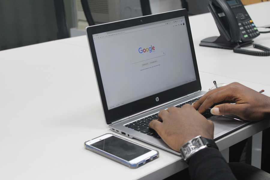 Google search screen of laptop with user hands on keyboard