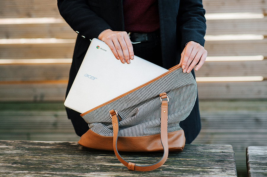 Close up of woman's hands putting chromebook laptop in bag