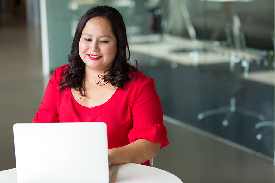 Woman on Laptop in bright red blouse