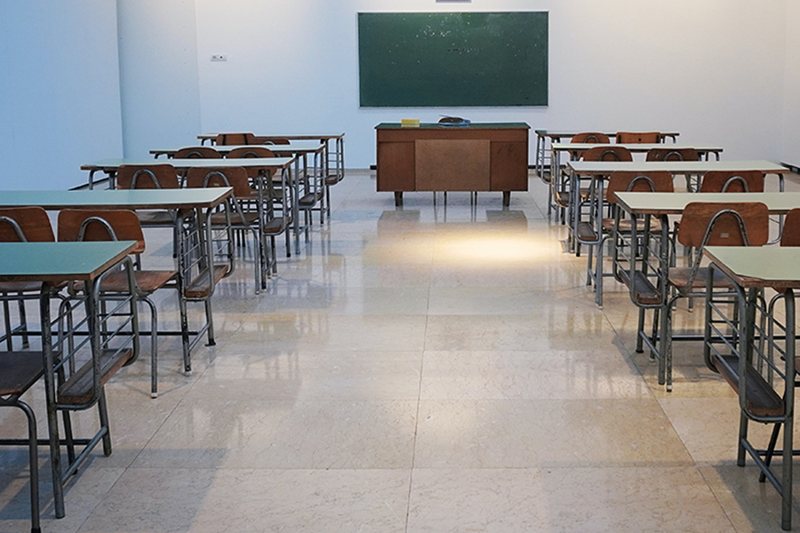 Large empty classroom with chalkboard at front of room